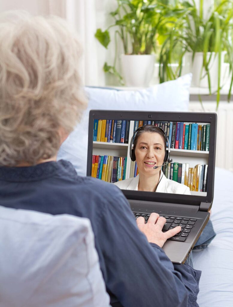 Woman in teletherapy session on a laptop